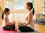 Caucasian mother and daughter practicing yoga