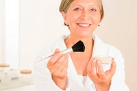 Mature woman hold brush and make_up powder