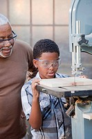 African American grandfather watching grandson use table saw