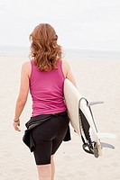 Caucasian woman carrying surfboard