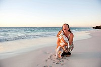 Woman and pet dog happy at beach