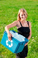 Recycling paper box businesswoman in sunny meadow