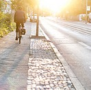 Cyclist driving towards the sun