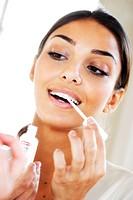 Woman applying a bleaching gel on her teeth.