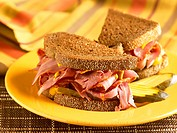Corned Beef Sandwich with Mustard and Pickles on Pumpernickel Bread, Halved on a Yellow Plate