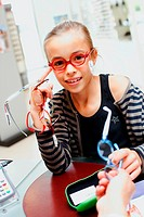 9 years old girl trying prescription glasses at the optician.
