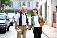 Senior couple walking in the street.