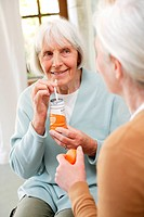 Elderly woman drinking energy drink to prevent denutrition.