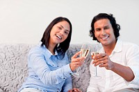 Couple celebrating with sparkling wine on the couch