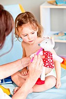 Therapeutic games : pediatrician examining the stuffed toy of a 3 years old girl.