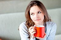 Woman drinking hot beverage.