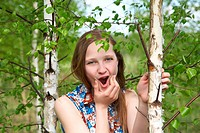 girl among young birches with a grimace