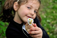 Girl holding bunch of daisies