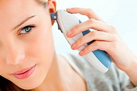 Woman taking her temperature with a digital tympanic thermometer
