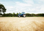 Tractor driving in tilled crop field