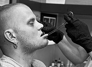 Rockland, Maine: July 29, 2008. Tracy Baker, an apprentice piercer at a tattoo parlor in Rockland, Maine, pierces the lip of Sean Jeweii, her body pie...
