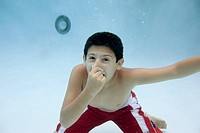 Boy holding nose underwater