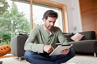 Germany, Bavaria, Nuremberg, Mature man using digital tablet in living room