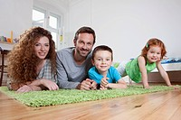 Germany, Berlin, Family relaxing on floor, smiling, portrait