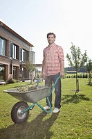 Germany, Bavaria, Nuremberg, Mature man with wheelbarrow in garden