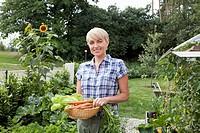 Germany, Bavaria, Nuremberg, Mature woman with vegetables in garden (thumbnail)