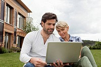 Germany, Bavaria, Nuremberg, Mature couple using laptop in garden
