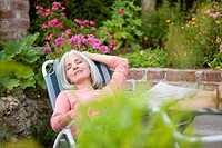 Germany, Bavaria, Mature woman relaxing in garden