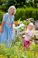 Germany, Bavaria, Mature woman with girl in garden (thumbnail)