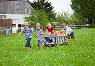 Germany, Bavaria, Group of children playing with hand cart in front of farmhouse (thumbnail)
