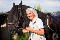 Germany, Bavaria, Mature woman hugging horse