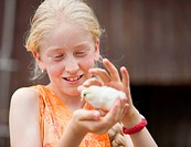 Germany, Bavaria, Girl with baby chick, close up