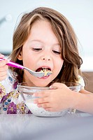 Germany, Girl eating muesli in kitchen
