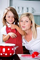 Germany, Mother and daughter eating noodles in kitchen (thumbnail)