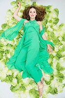 Young woman lying on salad