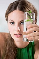 Germany, Young woman holding glass of water