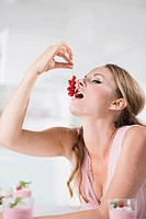 Germany, Young woman eating currants