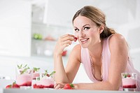 Germany, Young woman holding strawberry, smiling