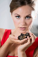Germany, Young woman holding truffles, close up