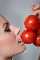 Young woman kissing tomatoes, close up