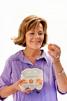 Senior woman holding eggs, close up (thumbnail)