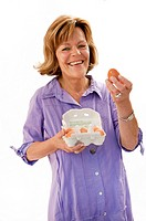 Senior woman holding eggs, smiling, portrait (thumbnail)