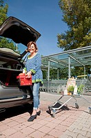 Germany, Munich, Senior woman stowing basket in car trunk
