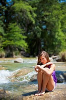 USA, Texas, Young woman sitting at Frio river