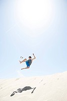 France, Teenage boy jumping on sand dune after football