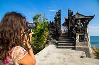 Indonesia, Tourist taking photograph of Batu Bolong Temple