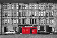 Traditional sandstone tenement building with a red fronted shop, Govan, Glasgow, Scotland UK
