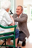 General practitioner talking with an elderly person during a visit in a retirement home.