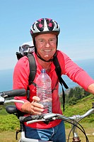 Cheerful senior man on mountain bike ride
