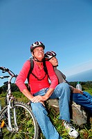 Senior couple riding mountain bikes in natural landscape