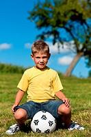 Junge mit Fußball sitzt auf einer Wiese
